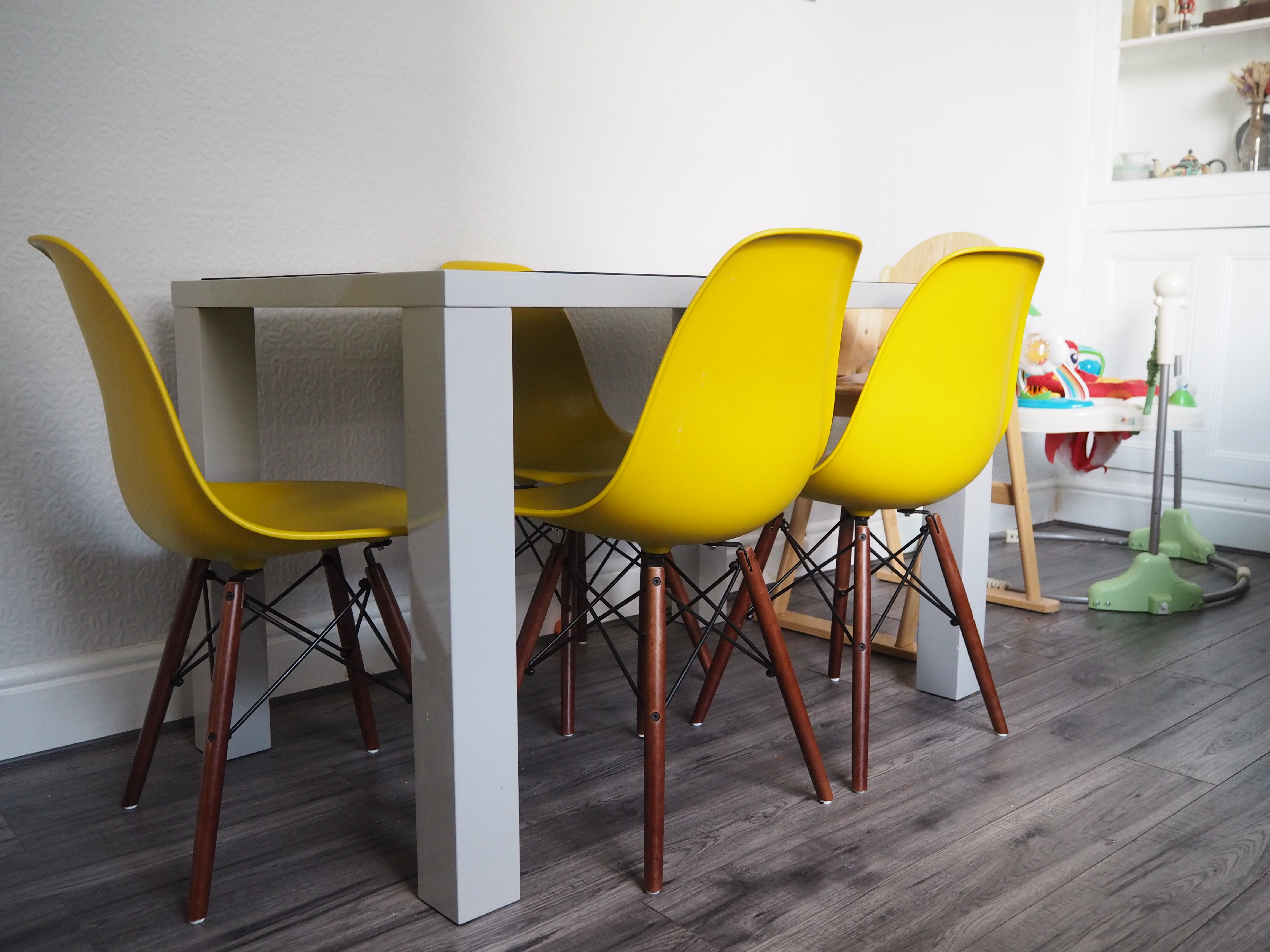 Grey gloss dining table yellow Charles Eames style chairs